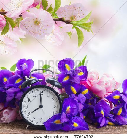 Spring time concept - retro alarm clock with fresh iris and tulips flowers