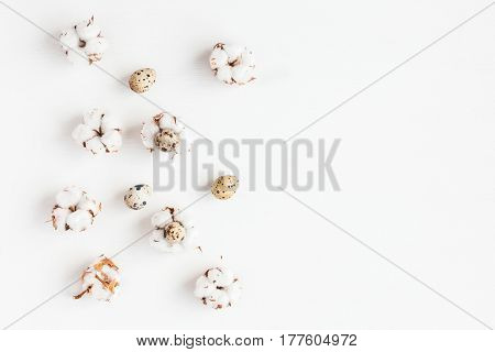 Easter quail eggs and cotton flowers on white background. Easter concept. Flat lay top view