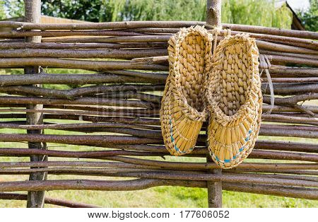 Bast Shoes On Wicker Fence