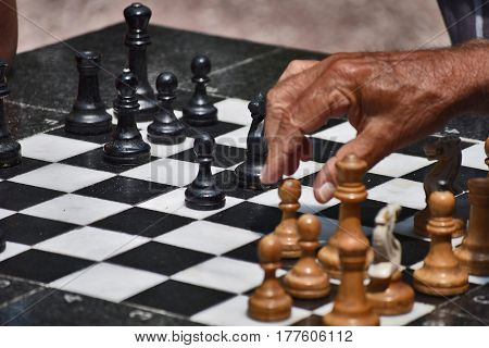 hands of the old man and chess board with white and black chess pieces