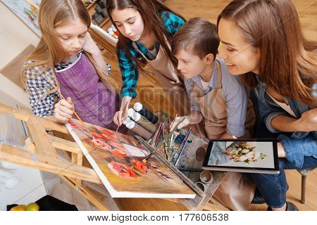 Enjoying art lesson . Positive helpful attentive teacher sitting in the art school and expressing joy while teaching painting kids and using gadget