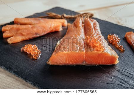 Smoked salmon fish on a slate board with caviar. Top view at cutted slices of smoked salmon