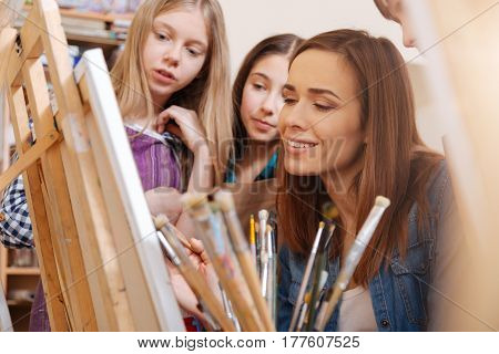 Sharing inspiration. Involved skillful gifted artist sitting in the art studio and expressing positivity while teaching art kids and painting poster