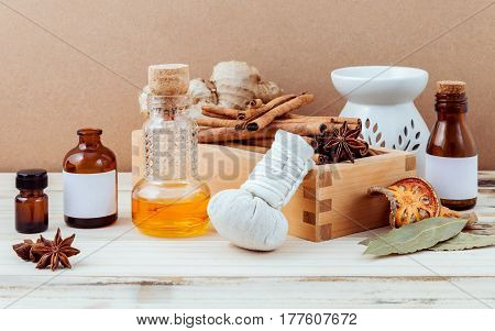Bottle of essential oil for ayurveda massage with cinnamon stick star anise bay leaves ginger root and herbal compress ball with selective focus on shabby wooden background .