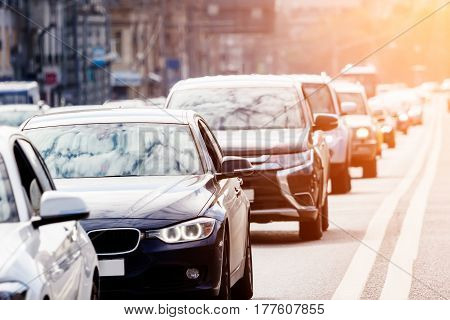 Cars in a long queue on the busy city street with sunlight