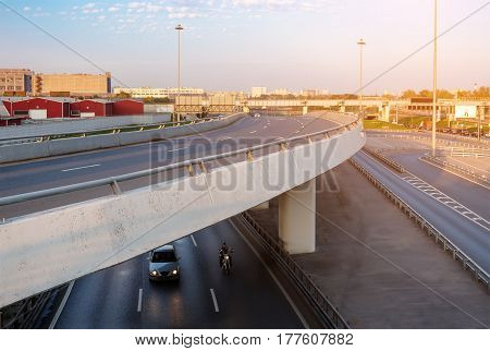 Overpass with car and motorbike underneath at sunset