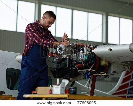 Technical worker repairing motor of jet before flight season