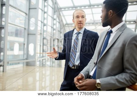 Portrait of two contemporary businessmen, one of them African, having conversation in  glass hall  of modern office building