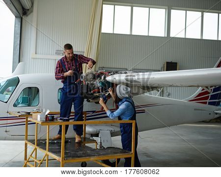 Male technician asking his female colleague for another wrench