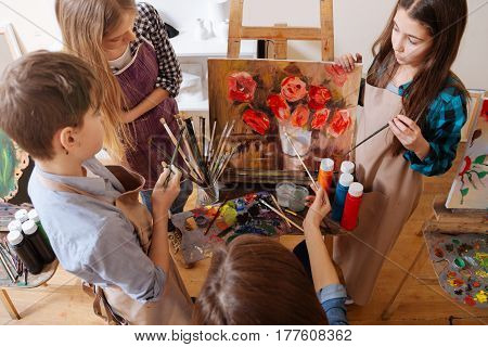 Mastering still life painting . Skilled proficient friendly teacher sitting in the art studio and expressing joy while teaching art kids and painting