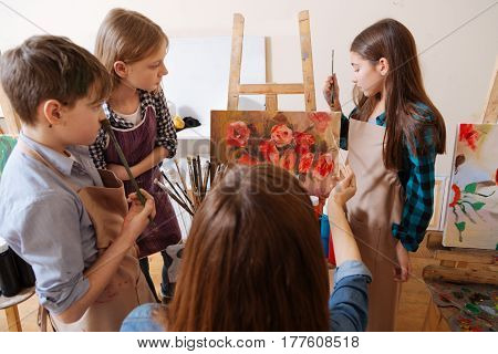 On our way to success. Skilled attentive thoughtful children standing in the art studio and expressing interest while studying art