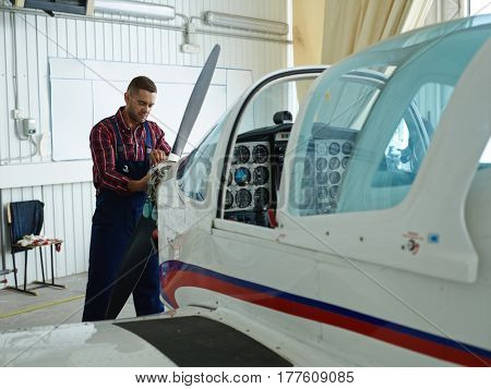 Young mechanic checking condition of airplane propeller