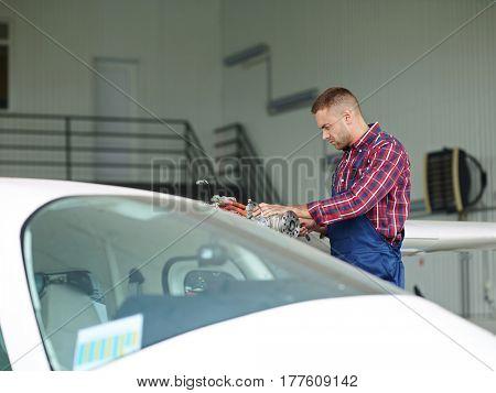 Young repairman in uniform working in hangar