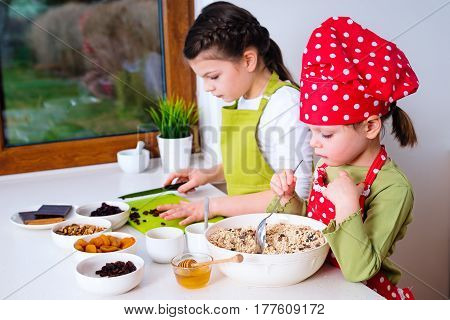 Two sisters preparing granola together. Happy siblings in the kitchen at home.