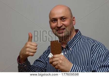young man eating a chocolate bar on a gray background