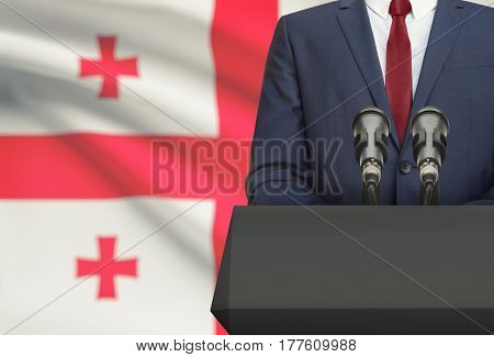Businessman Or Politician Making Speech From Behind A Pulpit With National Flag On Background - Geor