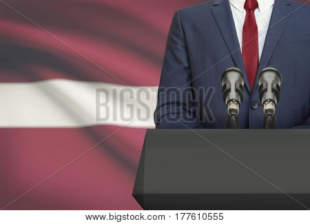 Businessman Or Politician Making Speech From Behind A Pulpit With National Flag On Background - Latv