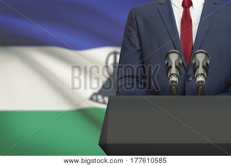 Businessman Or Politician Making Speech From Behind A Pulpit With National Flag On Background - Leso