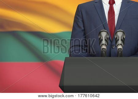 Businessman Or Politician Making Speech From Behind A Pulpit With National Flag On Background - Lith