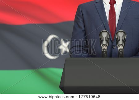 Businessman Or Politician Making Speech From Behind A Pulpit With National Flag On Background - Liby