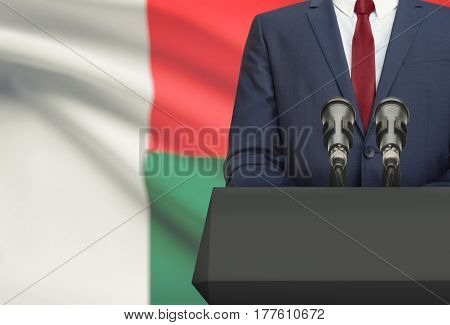 Businessman Or Politician Making Speech From Behind A Pulpit With National Flag On Background - Mada