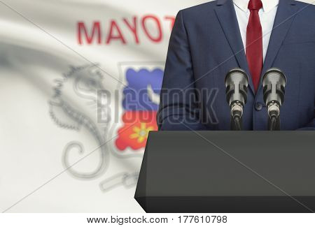 Businessman Or Politician Making Speech From Behind A Pulpit With National Flag On Background - Mayo