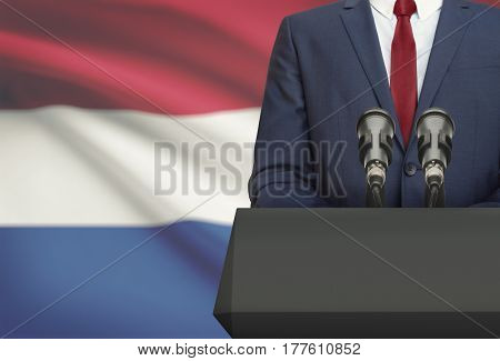 Businessman Or Politician Making Speech From Behind A Pulpit With National Flag On Background - Neth