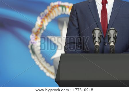 Businessman Or Politician Making Speech From Behind A Pulpit With National Flag On Background - Nort
