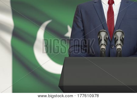 Businessman Or Politician Making Speech From Behind A Pulpit With National Flag On Background - Paki