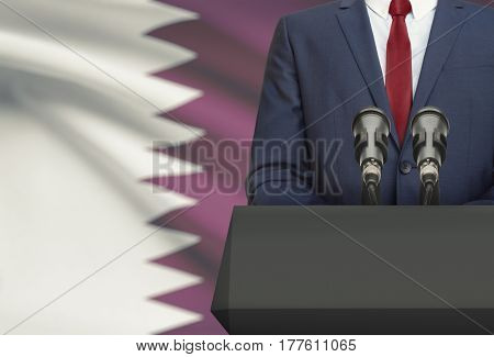 Businessman Or Politician Making Speech From Behind A Pulpit With National Flag On Background - Qata