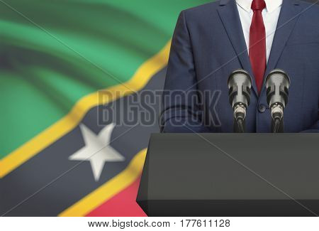 Businessman Or Politician Making Speech From Behind A Pulpit With National Flag On Background - Sain