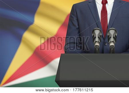 Businessman Or Politician Making Speech From Behind A Pulpit With National Flag On Background - Seyc