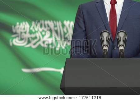 Businessman Or Politician Making Speech From Behind A Pulpit With National Flag On Background - Saud