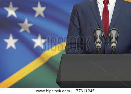Businessman Or Politician Making Speech From Behind A Pulpit With National Flag On Background - Solo