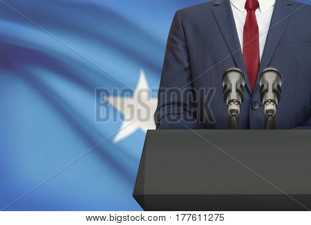 Businessman Or Politician Making Speech From Behind A Pulpit With National Flag On Background - Soma