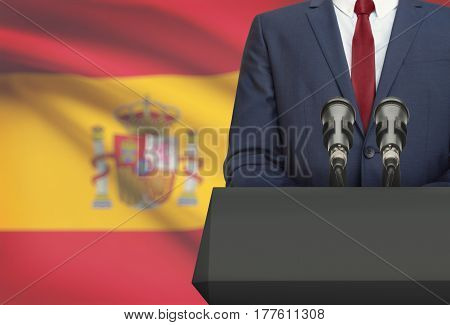 Businessman Or Politician Making Speech From Behind A Pulpit With National Flag On Background - Spai