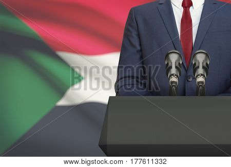 Businessman Or Politician Making Speech From Behind A Pulpit With National Flag On Background - Suda