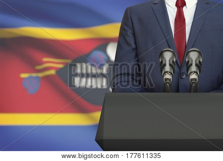 Businessman Or Politician Making Speech From Behind A Pulpit With National Flag On Background - Swaz