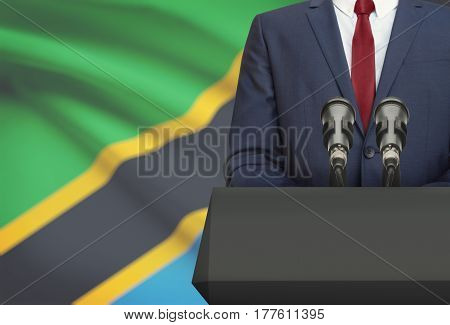 Businessman Or Politician Making Speech From Behind A Pulpit With National Flag On Background - Tanz