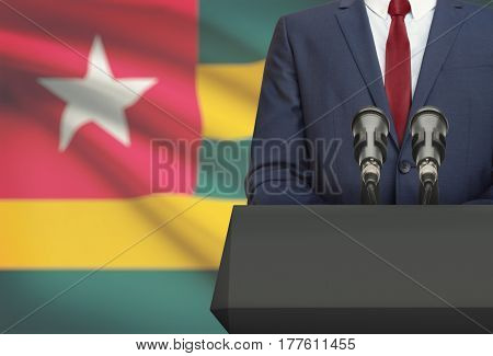 Businessman Or Politician Making Speech From Behind A Pulpit With National Flag On Background - Togo