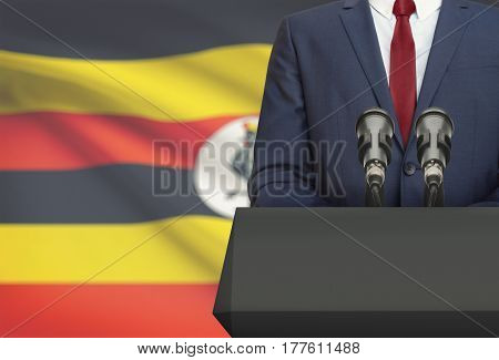 Businessman Or Politician Making Speech From Behind A Pulpit With National Flag On Background - Ugan