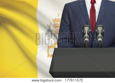 Businessman Or Politician Making Speech From Behind A Pulpit With National Flag On Background - Vati