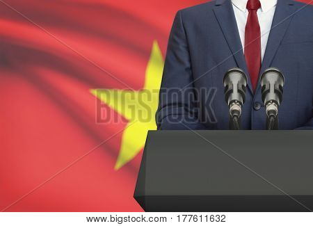 Businessman Or Politician Making Speech From Behind A Pulpit With National Flag On Background - Viet