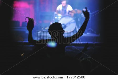 Rear View Of A Man With Raised Arms Enjoying A Concert