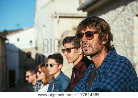 Row of young trendy people wearing sunglasses and looking away on background of old city street.