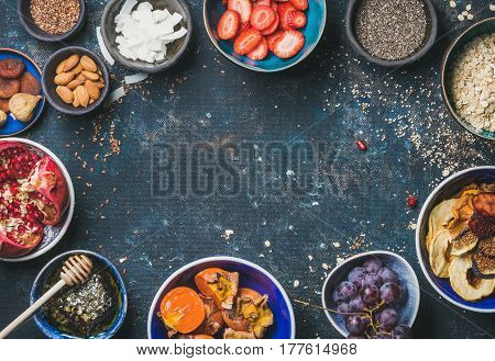 Ingredients for healthy breakfast over dark blue shabby background, top view, copy space. Fresh and dried fruit, chia seeds, oatmeal, almonds, honey. Clean eating, vegan, healthy food, dieting concept