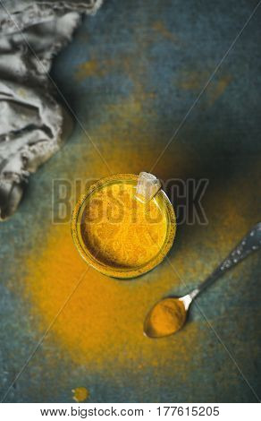 Golden milk with turmeric powder in glass over dark background, top view, copy space. Health and energy boosting, flu remedy, natural cold fighting drink. Clean eating, dieting, weight loss concept