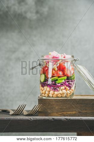 Healthy take-away lunch jar. Vegetable and chickpea sprout layered vegan salad in glass jar, grey concrete wall background, copy space, selective focus. Clean eating, vegetarian, raw, dieting concept