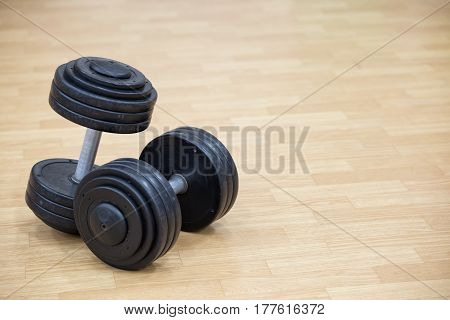 Background on the theme of sport with dumbbells on the floor of the gym