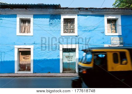 PANJIM, INDIA - FEB 25, 2017: Blue walls of historical houses and motion blur from fast driving indian rickshaw on February 25, 2017. Near 5 million tourists visit Goa annually
